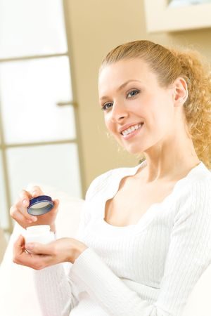 Young happy woman with cosmetic cream at home photo