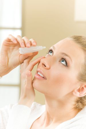 Photo of young woman dripping eye with eyes drops photo