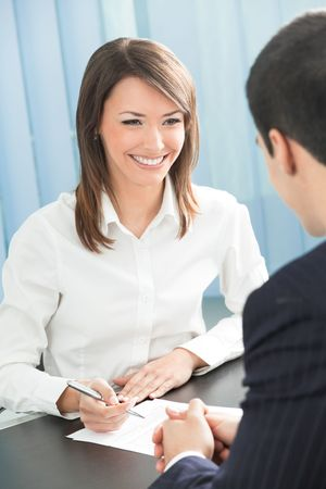 Two businesspeople, or business person and client, with document at office Stock Photo - 4833607