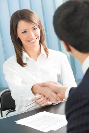 n�gocier: Deux hommes d'affaires, ou des gens d'affaires et les clients au bureau handshaking