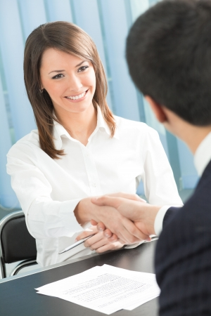 Two businesspeople, or business person and client handshaking at office Stock Photo - 4833605