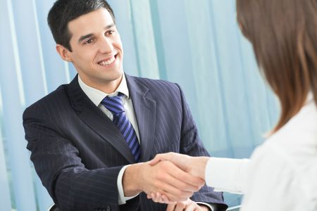 Two happy businesspeople handshaking, or business person and client at office photo