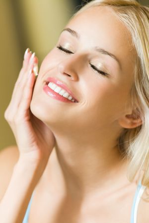 moisturizing: Smiling woman applying cream on face at home