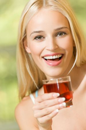 Happy young woman with glass of garnet juice photo