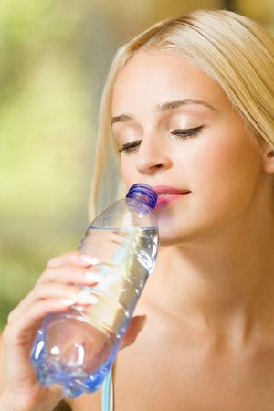 Woman with bottle of water, outdoors photo