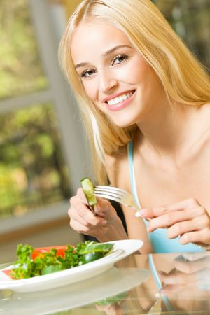 Young happy smiling woman eating salad at home Stock Photo - 4983305