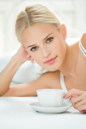 Happy woman with cup of coffee or tea at bedroom photo