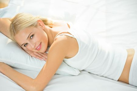 Young happy smiling woman waking up at bedroom photo