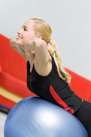 Young happy woman doing exercises with fitball photo