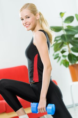 Young happy woman doing exercises with dumbbells at home photo