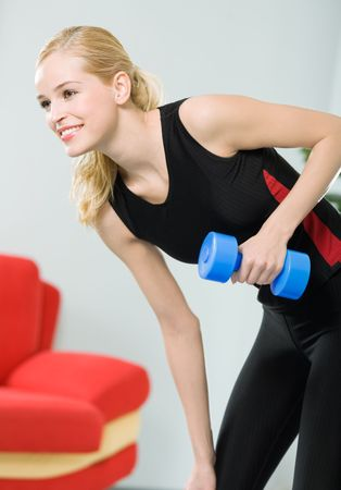 Young happy woman doing exercises with dumbbell at home photo