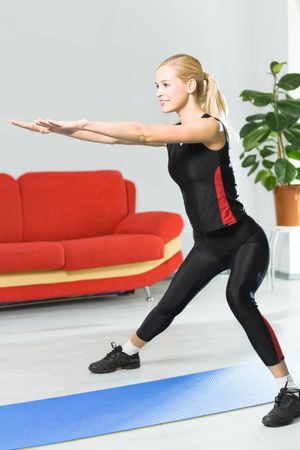 Young happy woman doing fitness exercises at home photo