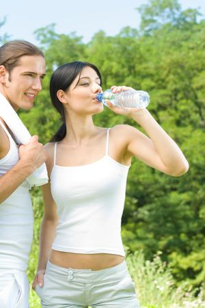 Happy couple with bottle of water, on outdoor workout photo