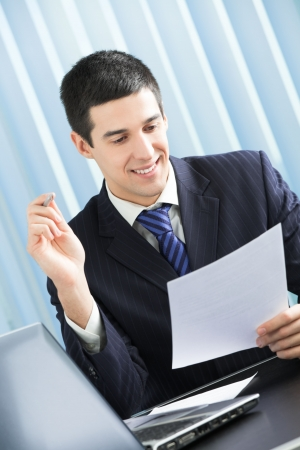 signing document: Happy businessman reading document at office Stock Photo