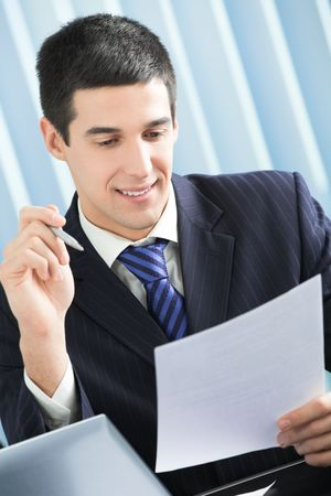Happy businessman reading document at office photo