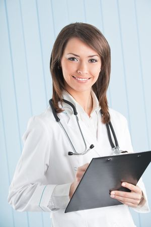 Happy doctor or nurse with clipboard at office photo