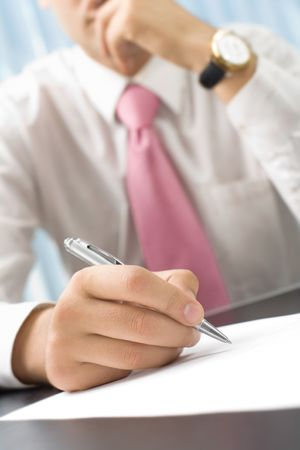 25 30: Businessman writing or signing document at office. Focus on hand with pen.