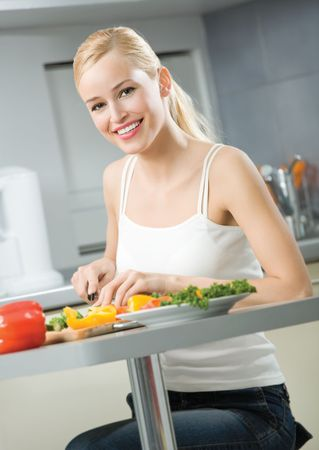 Young happy smiling woman cooking salad at home Stock Photo - 5406062