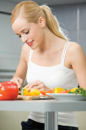 Young happy smiling woman cooking salad at home photo