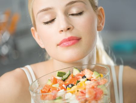 Young happy smiling woman with salad at home photo