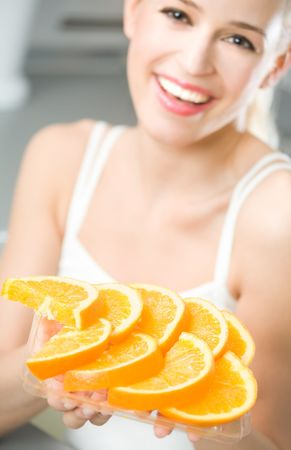Young happy woman with plate of orange. Focus on plate. Stock Photo - 5406061