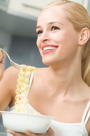 Happy woman eating spaghetti at home photo