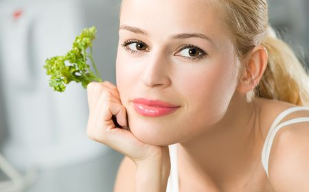 Young woman with parsley at domestic kitchen photo