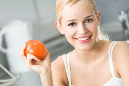 Young woman with tomato at domestic kitchen photo