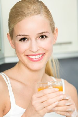 Happy young woman with juice of tropical fruit photo