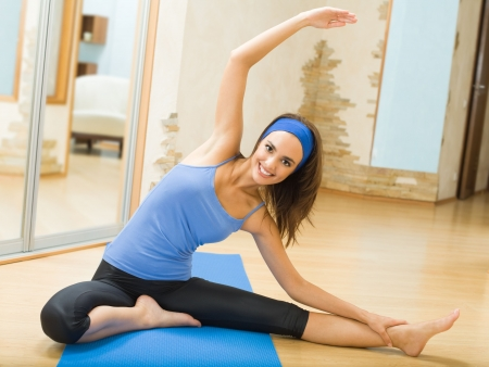 girl in sportswear: Young happy woman exercising at home