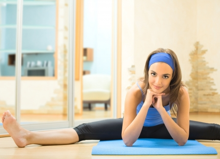 home gym: Young happy woman exercising at home