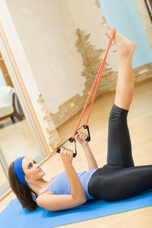 Young happy woman exercising with expander at home photo