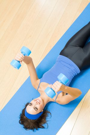 Young happy woman exercising with dumbbells at home Stock Photo - 5484264