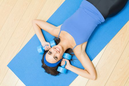 Young happy woman exercising with dumbbells at home Stock Photo - 5484273