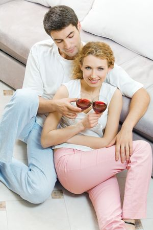 Young couple celebrating with red wine at home photo