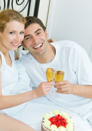 Young couple celebrating with champagne at bedroom photo