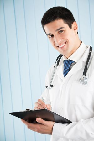 Happy doctor with pen and clipboard at office photo