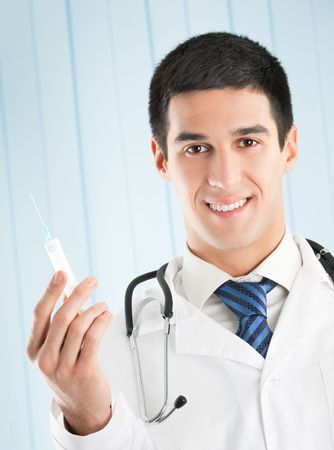 Happy doctor with syringe at office photo