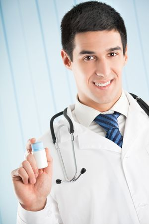 Happy doctor with pill and at office photo