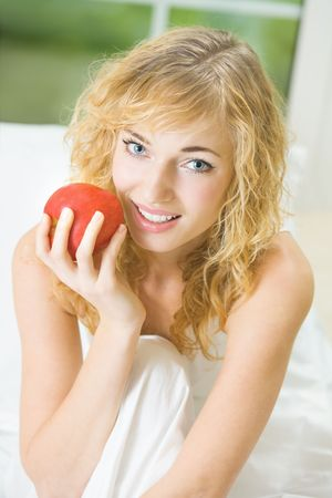 Happy young woman with apple at home photo