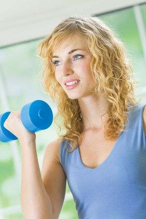 Young happy woman exercising with dumbbell at home photo