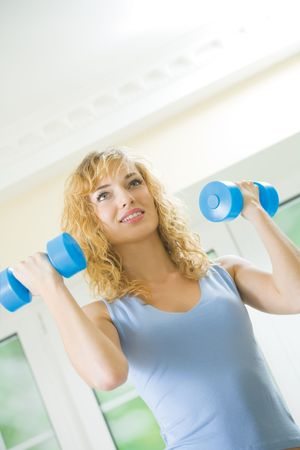 Young happy woman exercising with dumbbells at home Stock Photo - 5595804