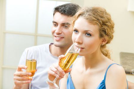25s: Young couple celebrating with champagne at home Stock Photo