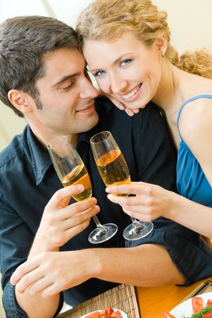 Young couple celebrating with champagne at home photo