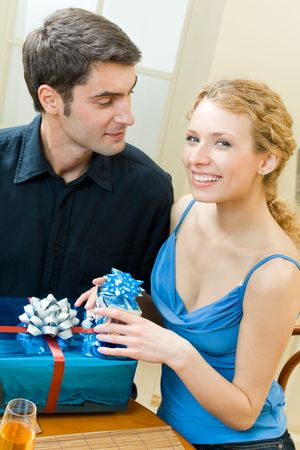 Young couple celebrating with champagne and gifts at home photo