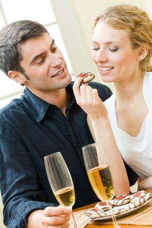 pareja comiendo: Pareja joven amorosa comer galletas juntos en casa