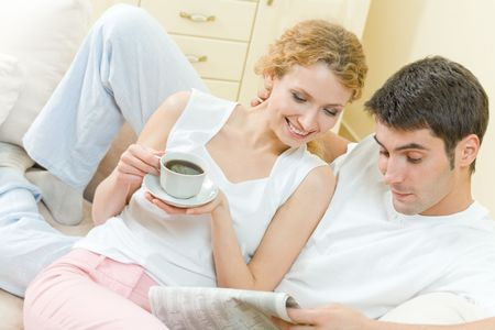Couple reading announcements in newspaper together at home photo