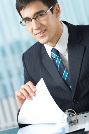 Happy businessman with documents at office photo