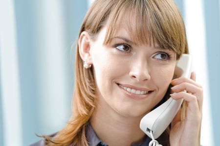 Portrait of happy businesswoman with phone at office photo