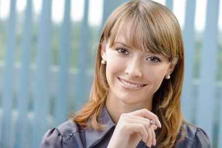 Portrait of happy businesswoman with pen at office photo